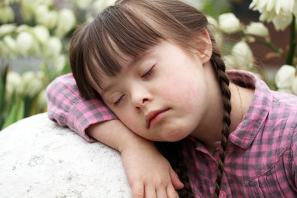 Portrait of beautiful young girl sleeping outside on flowers background